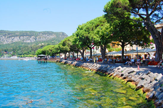 The busy promenade in beautiful Garda town, filled with tourists basking in the sunshine.